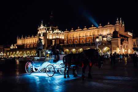 The old square of the night krakow with luminous horse-drawn carriages