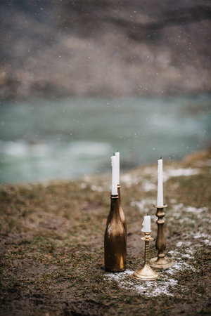 Candles in a bottle on the ground against a waterfall background