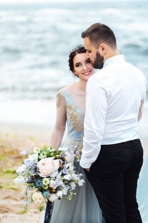 same couple with a bride in a blue dress walk along the ocean shore