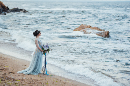 bride with a bouquet of flowers on the beach near the water Banque d'images - 119283767