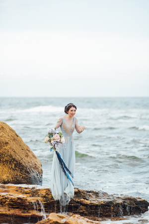 bride with a bouquet of flowers on the beach near the water Banque d'images - 119283769