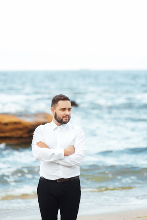 the groom in a white shirt and black pants stands on the beach