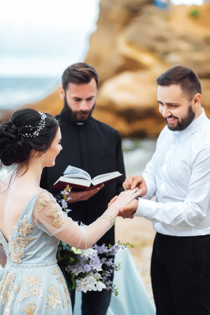 wedding couple on the ocean with a priest Banque d'images - 119283782