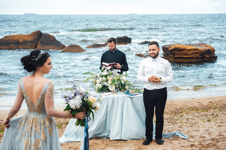 wedding couple on the ocean with a priest Banco de Imagens