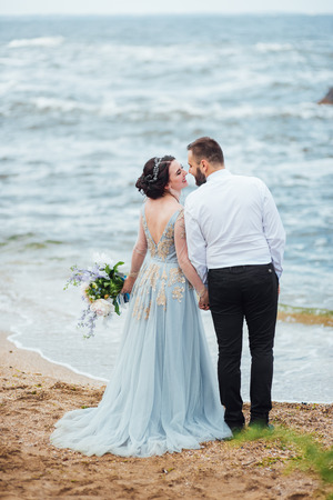 same couple with a bride in a blue dress walk along the ocean shore Banque d'images - 119283790