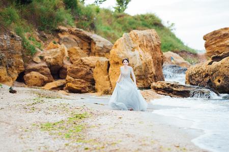 bride in a blue light dress walking along the ocean