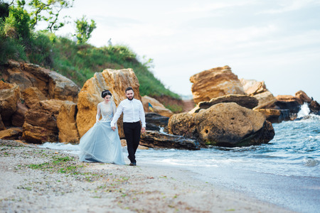 same couple with a bride in a blue dress walk along the ocean shore Banque d'images - 119009269