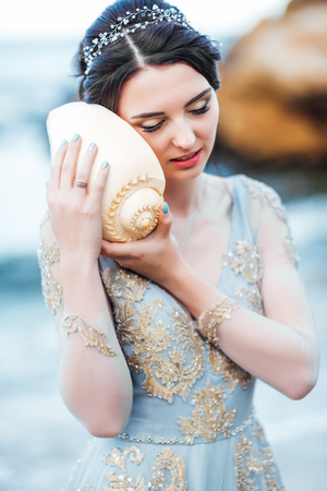 bride with a big shell on the beach in a blue wedding dress Banque d'images - 119009272