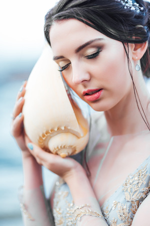 bride with a big shell on the beach in a blue wedding dress Banque d'images - 119009284