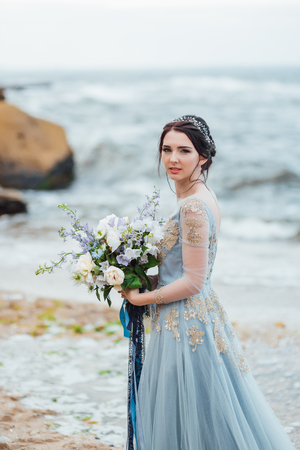 bride with a bouquet of flowers on the beach near the water