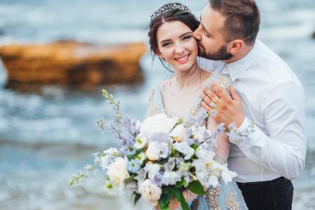 same couple with a bride in a blue dress walk along the ocean shore