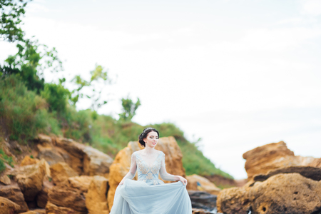 bride in a blue light dress walking along the ocean