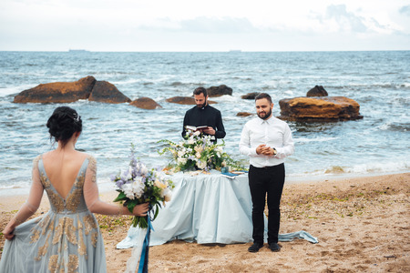 wedding couple on the ocean with a priest Banque d'images - 119010278