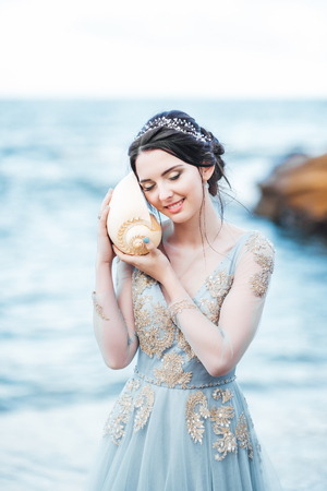 bride with a big shell on the beach in a blue wedding dress Banque d'images - 119010416