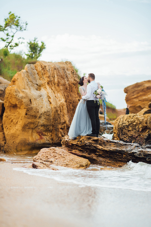 same couple with a bride in a blue dress walk along the ocean shore Banque d'images - 119010417