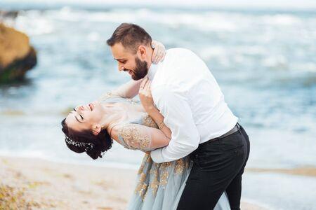 same couple with a bride in a blue dress walk along the ocean shore Foto de archivo