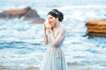 bride with a big shell on the beach in a blue wedding dress