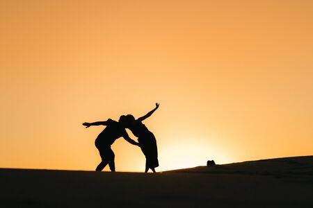 silhouettes d'un jeune couple heureux et fille sur fond de coucher de soleil orange dans le désert de sable