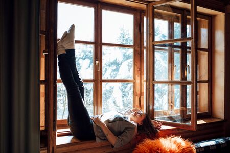 girl in the house near the window overlooking a snowy landscape
