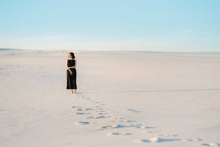 girl in a black dress stands in the middle of the desert against the background of footprints 版權商用圖片