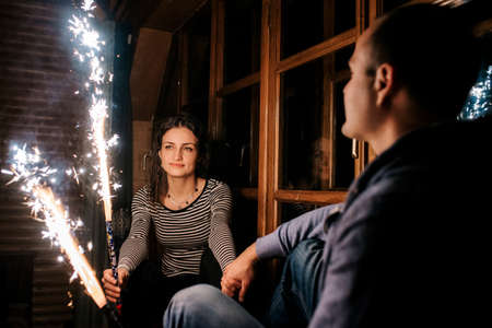 guy and a girl lit sparklers inside a wooden house late at night