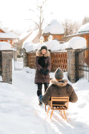 girl carries a guy on a sled on a snowy street on a sunny day