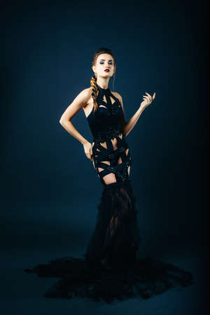 white girl modell on a dark background in a dress made of cut stripes of black fabric