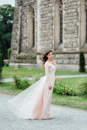 A girl in a light pink dress against the background of a medieval Polish stone castle Imagens