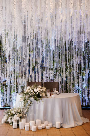 The presidium of the newlyweds in the banquet hall of the restaurant is decorated with candles and green plants, wisteria hangs from the ceiling