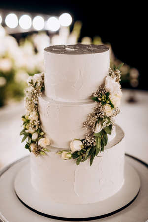 wedding white cake on a high stand near the white podium with green decor