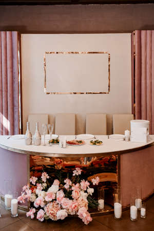 the presidium of the newlyweds in the banquet hall of the restaurant is decorated with candles and green plants, the general tone of the hall is beige