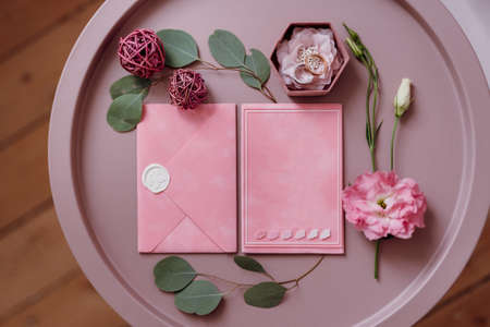 pink wedding invitation in a gray envelope on a table with green sprigs