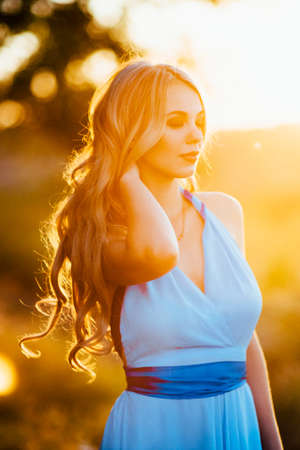 blonde with loose hair in a light blue dress in the light of sunset in nature