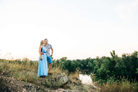 blonde girl with loose hair in a light blue dress and a guy in the light of sunset in nature