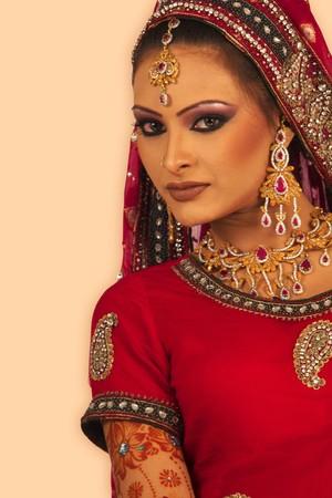 south asians: Slim beautiful woman wearing luxurious wedding dress over white studio background
