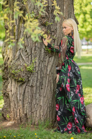 Beautiful young girl in a beautiful dress stands near a tree and looks aside