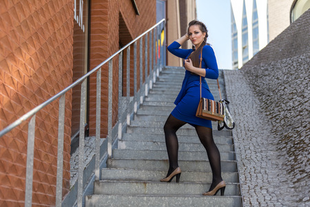 A young girl is standing on the stairs with a female handbag Banco de Imagens