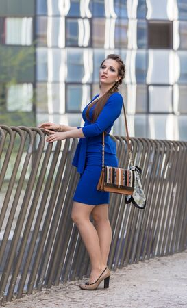 Beautiful strongly young woman in the city with handbag