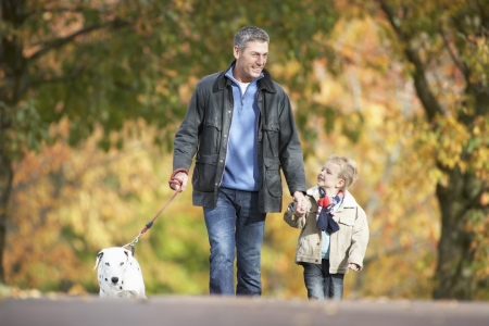 Man With Young Son Walking Dog Through Autumn Park