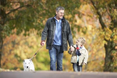 autumn dog: Man With Young Son Walking Dog Through Autumn Park
