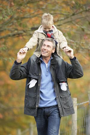 Man With Young Son On Shoulders Autumn Park photo