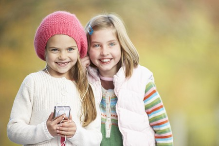 Two Young Girl Outdoors With MP3 Player photo