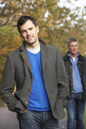 homosexuales: Dos hombres permanente Outside In Autumn Woodland