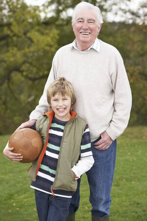 Grandfather With Grandson Holding Football Outside photo