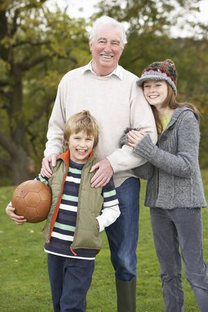 Grandfather With Grandchildren Holding Football Outside photo