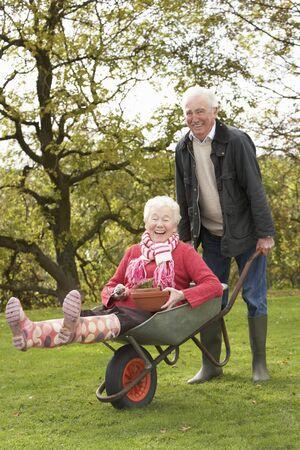 carretilla: Senior de pareja Man, Giving Ride de mujer en carretilla  Foto de archivo