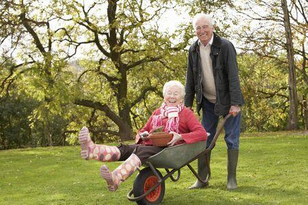 Senior Couple Man Giving Woman Ride In Wheelbarrow photo