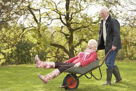 tercera edad: Senior de pareja Man, Giving Ride de mujer en carretilla  Foto de archivo