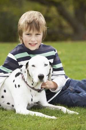 Young Boy Relaxing Outdoors With Pet Dog photo