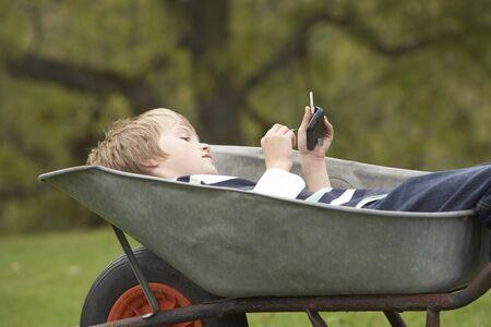 Young Boy Laying Wheelbarrow Using Smart Mobile Phone photo